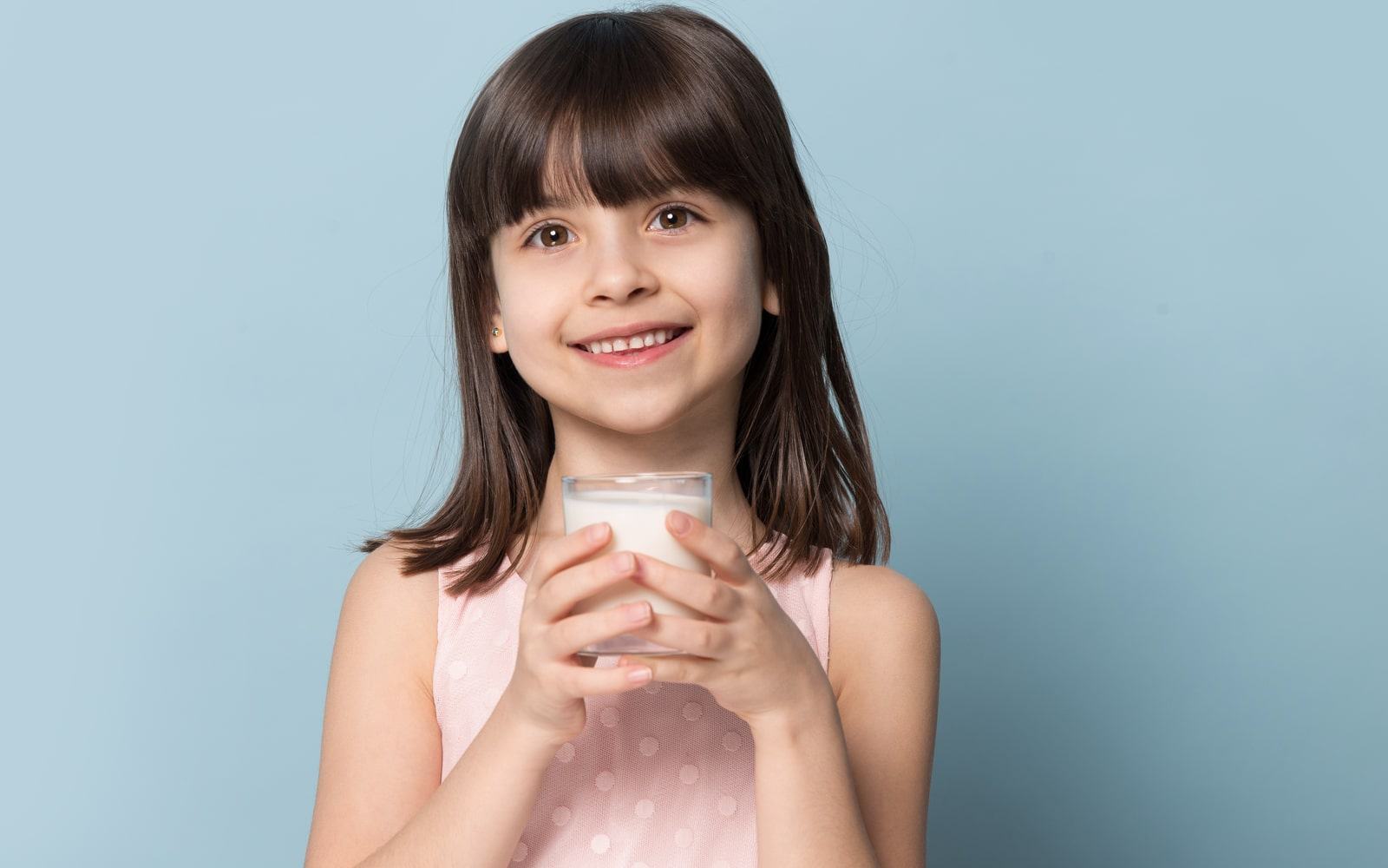 Smiling child holding glass of milk